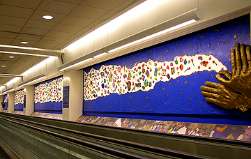 An 80 foot long cloud of 1200 child-created ceramic objects connects two sets of open hands at Philadelphia International Airport.