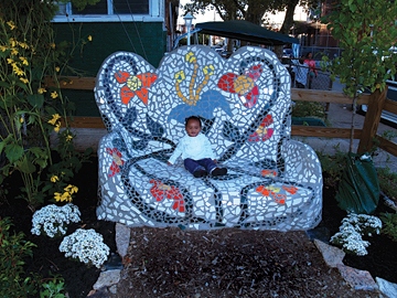 "Surrounded by flowers, a toddler sits on an oversized tile mosaic ""couch"" in COSACOSA's North Philadelphia Healing Garden."
